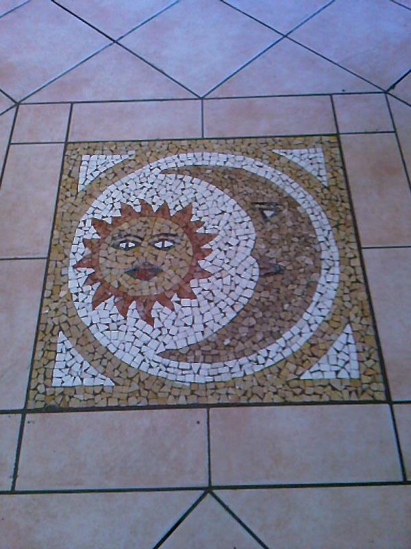 Particolare di inserto in mosaico nel pavimento ceramico